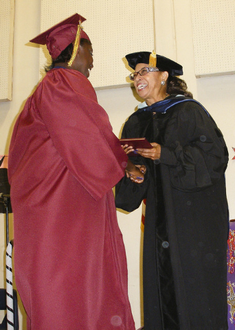 Clark County School Board Vice President Linda Young, right, presents a diploma to Simone Taylor, valedictorian of the 2014 adult high school class of Nevada's only female prison, Florence McClure ...