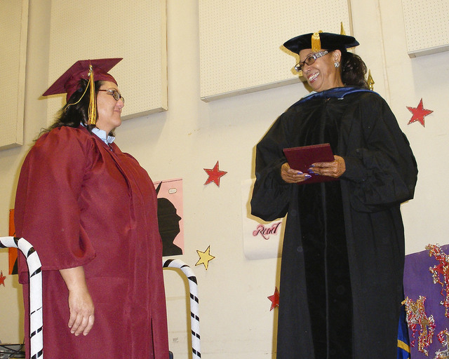 An inmate receives her high school diploma from Clark County School Board Vice President Linda Young, right, at  the 2014 adult high school graduation ceremony  at Florence McClure Women's Correct ...