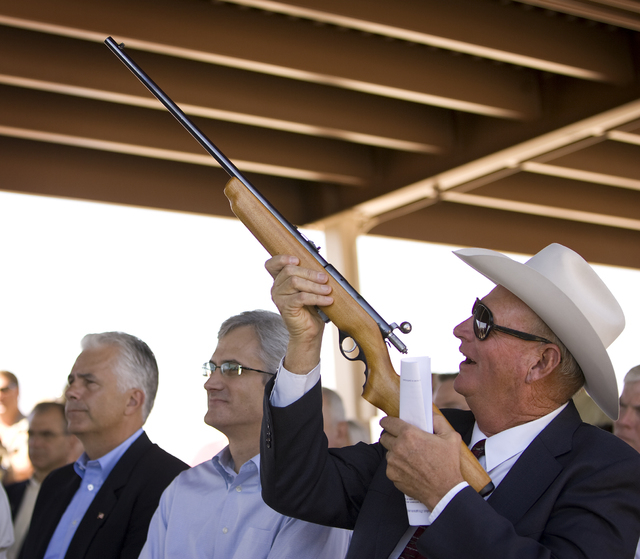 Clark County Commissioner Tom Collins, right, looks over a rifle owned by Senate Majority Leader Harry Reid, D-Nev., as he stands next to Reid's son, Clark County Commission Chairman Rory Reid, ce ...