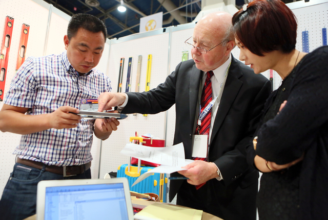 Attorney Peter Jansson, center, explains trademark infringement to representatives working at the Jinhau Chunyi Tools Co., Ltd. booth during the National Hardware Show at Las Vegas Convention Cent ...