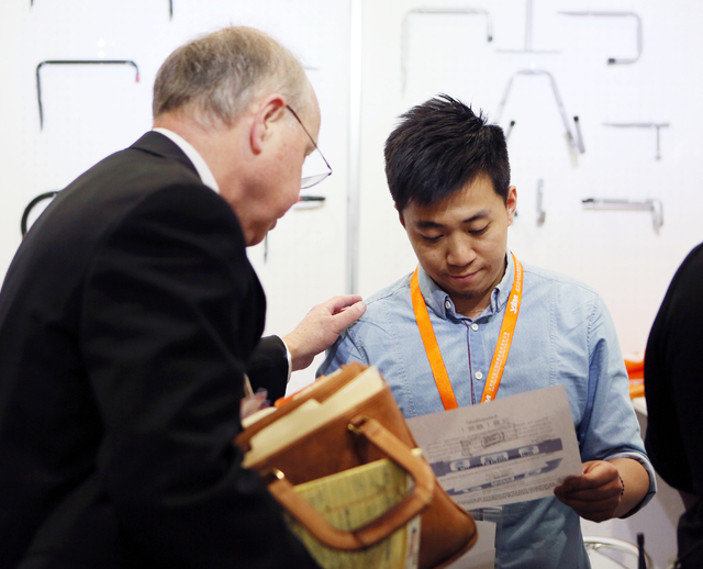 Attorney Peter Jansson, left, explains trademark infringement to a representative working at the Wuxi Just International Trading Co., Ltd. booth during the National Hardware Show at Las Vegas Conv ...