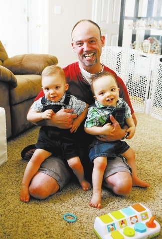 Kevin Zelenka holds his 16-month-old twins Gavin, left, and Carter in his home Wednesday, May 28, 2014, in Las Vegas. Zelenka is a stay-at-home dad and writes on his blog doulbetroubledaddy.com in ...