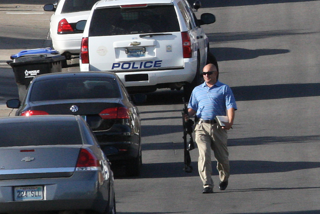 Henderson police investigate the crime scene after an officer was hospitalized Wednesday morning when he was shot or struck by shrapnel during a fatal officer-involved shooting. June 11, 2014 (Mic ...