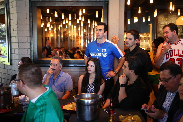 "State Sen. Ruben Kihuen, D-Las Vegas, center, watches the game during his ""Soccer with the Senator"" event for supporters featuring a watch party for the Mexico vs. Brazil World Cup game  ..."