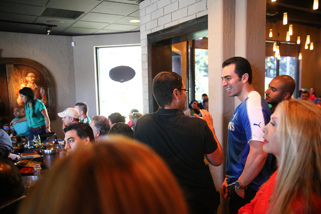 "State Sen. Ruben Kihuen, D-Las Vegas, right, in blue, mingles with the crowd during his ""Soccer with the Senator"" event for supporters featuring a watch party for the Mexico vs. Brazil W ..."