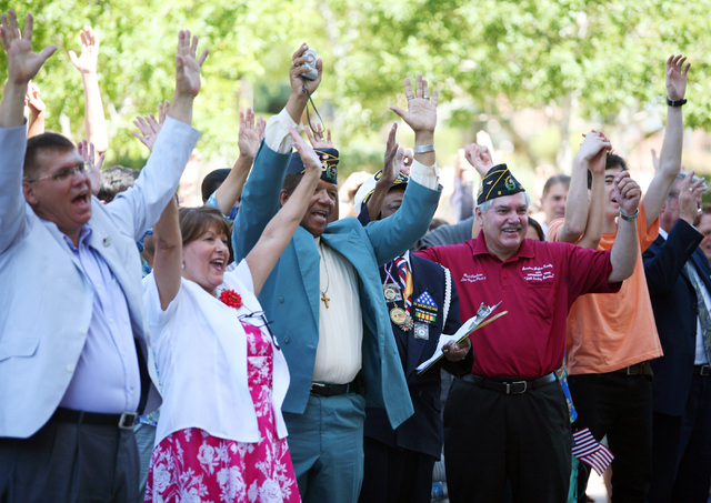 People cheer during a gathering of a Unification Church tour group and community members outside Grant Sawyer Building Wednesday, June 25, 2014, in Las Vegas. The church group is part of God&#x201 ...