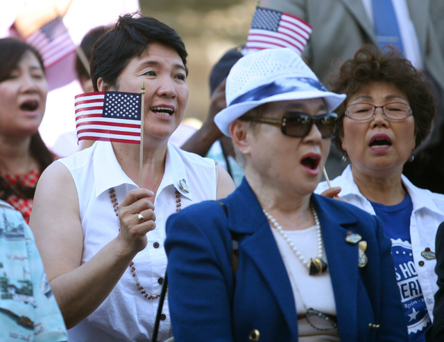 Yoko Lincoln, front left, of Omaha, Nebraska, sings during a gathering of a Unification Church tour group and community members outside Grant Sawyer Building Wednesday, June 25, 2014, in Las Vegas ...