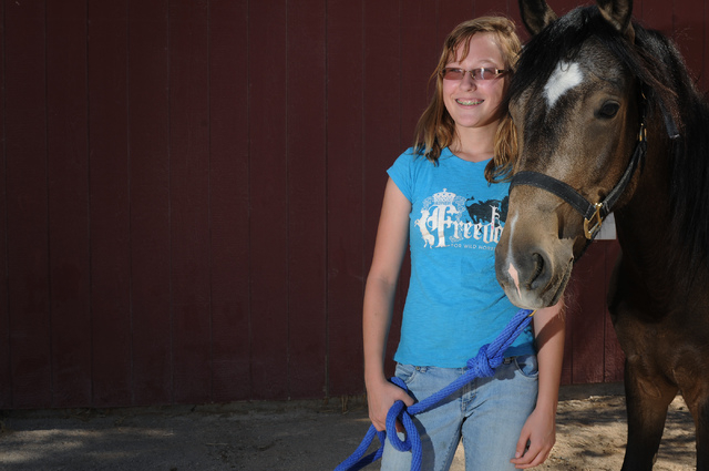 Robin Warren, 13, poses for a portrait with her rescued horse Rocky, a 2-year-old grulla horse at a friend's private ranch in Las Vegas Tuesday, June 24, 2014. Warren, with the help of her caregiv ...