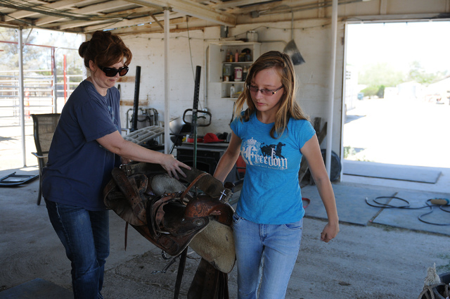 Robin Warren, right, 13, and her caregiver Denise DeLucia, carry a saddle to mount on a horse at a private ranch in Las Vegas Tuesday, June 24, 2014. Warren, with the help of her caregiver Denise  ...