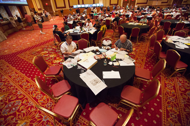 Robert Leclerc, right, and Gary Richard sit at a table before the start of the Belmont Stakes horse race in Elmont, N.Y., during a viewing party at South Point hotel-casino in Las Vegas on Saturda ...