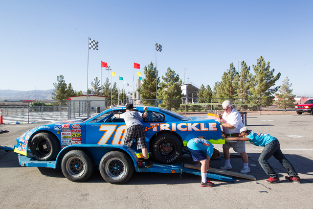 Chuck Trickle, second from right, prepares to unload the NASCAR Super Late Model which his son, Chris Trickle, drove, with the help of 11-year-old Dezel West, from left, Tommy Trickle, 11, and Tyr ...