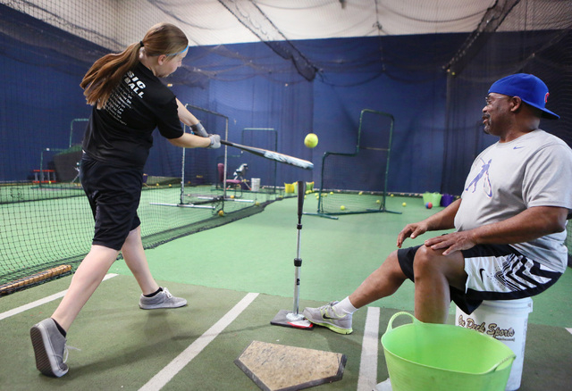 Bill Madlock, right, four-time Major League Baseball batting champion, instructs Lauren Powell, 12, during a private lesson at The Dugout indoor batting cages Thursday, June 19, 2014, in Las Vegas ...