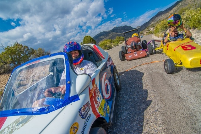 """The Gravity Cars are towed back to the top of the hill after a practice run. """"Bud Wiser"""" with Peta Singh and Majinder Singh in the background. (Courtesy Christopher Crews)"""