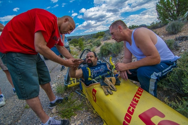 """Fellow racers Peta Singh and Vince """"Tinman"""" Hobbs assist Majinder after a high-speed rollover. He suffered a broken nose, broken hand and a concussion. (Courtesy Christopher Crews)"""