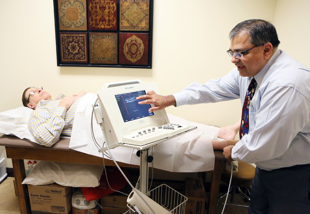 Dr. Kenneth Shah, right, explains the results of patient Rick Carter's, 69, left, previous ultrasound during a demonstration at Vascular Institute of Southern Nevada Tuesday, May 13, 2014,  ...