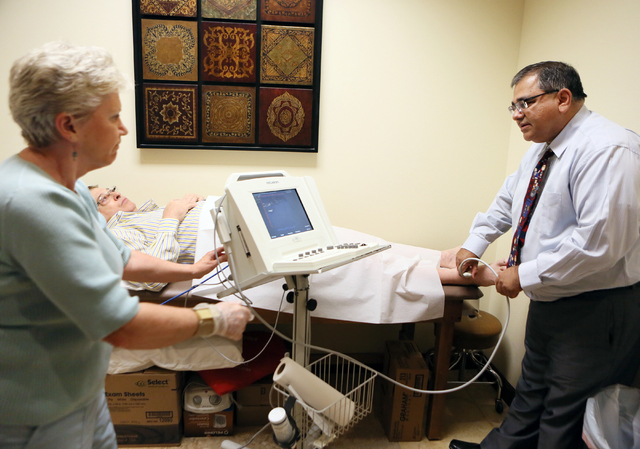 Dr. Kenneth Shah, right, demonstrates an ultrasound on patient Rick Carter, 69, center, at Vascular Institute of Southern Nevada Tuesday, May 13, 2014, in Henderson. Cardiovascular Ultrasound Tech ...