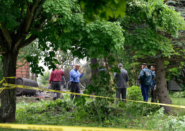 Investigators rope off the site of small airplane crash in the backyard of a home that killed the pilot on Tuesday, June 17, 2014, in East Patchogue, N.Y. A mother and infant inside the house in t ...