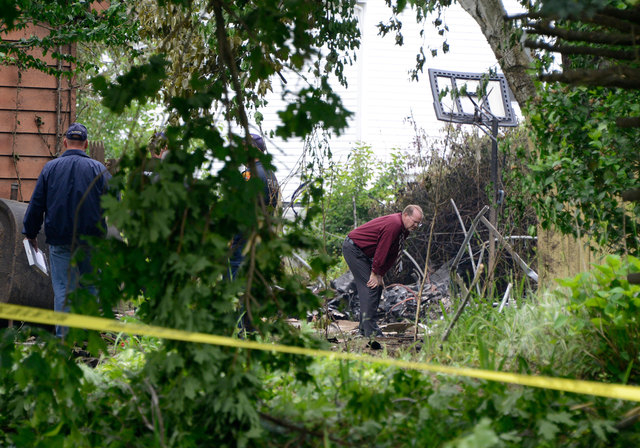 Investigators look over the site of small airplane crash in the backyard of a home that killed the pilot on Tuesday, June 17, 2014, in East Patchogue, N.Y. A mother and infant inside the house in  ...