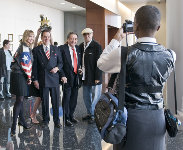 Mary Williams, right, of the U.S. Bureau of Citizenship and Immigration Services, takes a photo of comedian Rich Little, second left, surrounded by friends prior to his citizenship hearing in the  ...