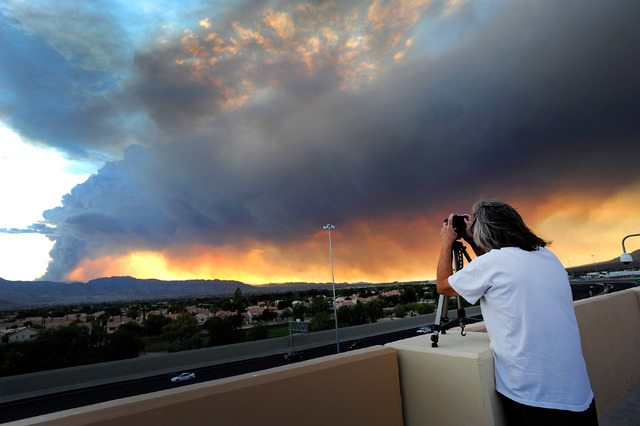 Jim. Czubak of Las Vegas photographs the billowing smoke from the Carpenter One fire on Friday, July 5, 2013.  Several hundred homes have been evacuated and conditions continue to worsen on Mt Cha ...