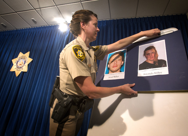 Metro officer Laura Meltzer, before a press conference at Metro Police Department on Monday, June 9 , 2014, places photos of the suspects, Jerad and Amanda Miller, in the shooting deaths of two of ...