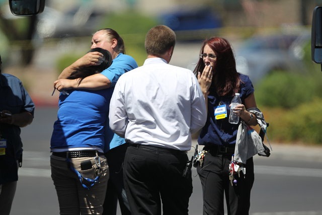Walmart employees hug outside their store after shootings left five people dead -- including two Las Vegas police officers -- at the store and a nearby CiCiճ Pizza at the corner of North Nel ...