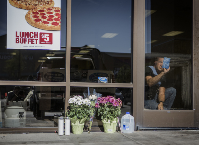A man cleans windows near a makeshift memorial at CiCi's Pizza store, 309 N. Nellis Blvd., on Monday, June 9, 2014. Officers Alyn Beck, 41, and Igor Soldo, 31, were in their seats at CiCi's Pizza  ...