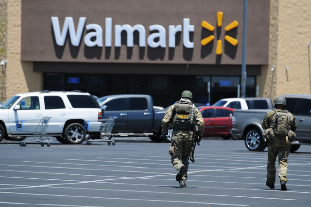 Two Las Vegas police officers rush to Walmart near Nellis Boulevard and Stewart Avenue where two suspects are confirmed to have shot two police officers Sunday, June 8, 2014. (Erik Verduzco/Las Ve ...