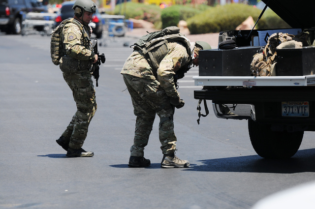 Two Las Vegas police officers gear up in front of Walmart near Nellis Boulevard and Stewart Avenue where two suspects are confirmed to have shot two police officers Sunday, June 8, 2014. (Erik Ver ...
