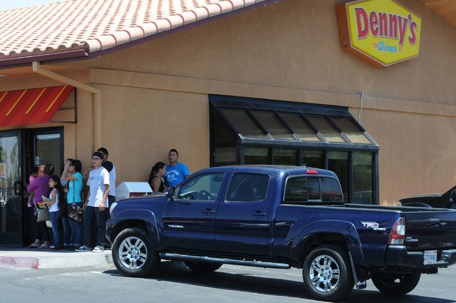 Bystanders watch the police activity across the street from Walmart near Nellis Boulevard and Stewart Avenue where two suspects are confirmed to have shot two police officers Sunday, June 8, 2014. ...