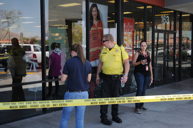 Walmart employees wait isolated from the public at Catherine's clothing store to be interviewed as witnesses following a police standout with two shooting suspects at Walmart near Nellis Boulevard ...