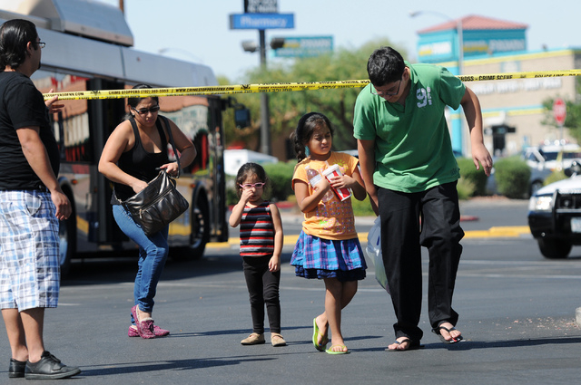 Witnesses from left, Erick Valdovinos, Blanca Sanchez, and her children Angie, 3, Daniela, 8, and Milton, 12, leave the scene at Walmart near Nellis Boulevard and Stewart Avenue in Las Vegas after ...
