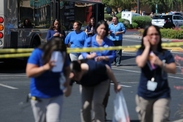 Walmart employees leave the scene near Nellis Boulevard and Stewart Avenue in Las Vegas where two shooting suspects are confirmed deceased after shooting two police officers Sunday, June 8, 2014.  ...