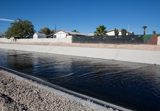 Cindy Sherwood 's back wall is painted black in an effort to ward off bugs from nearby Sloan Channel in North Las Vegas on Friday, June 27, 2014. Sherwood's family pool has remained empty since 20 ...