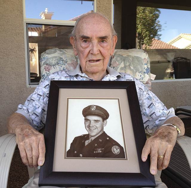Tom Norman, 92, holds his Army 15th Air Force photograph Thursday, June 5, 2014, at his Las Vegas home. He was a navigator-bombardier for a B-24 Liberator that flew secret missions to drop special ...