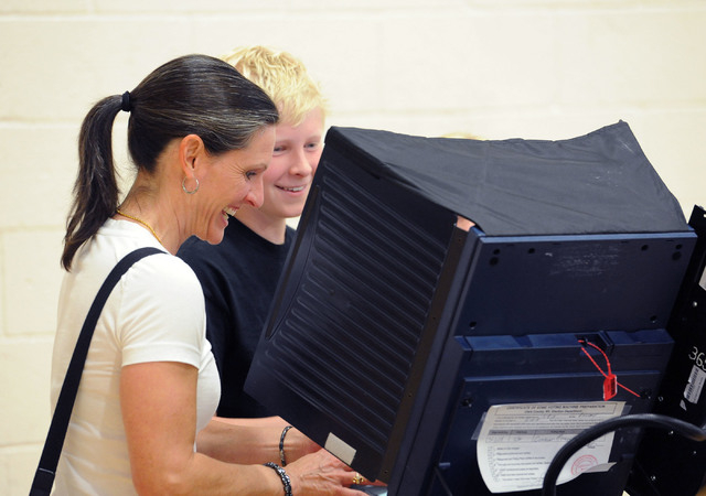 Darcy Bechtel laughs as she votes while showing her son, Jack, 12, the process at Cimarron-Memorial High School in Las Vegas, Tuesday, June 10, 2014. (Jerry Henkel/Las Vegas Review-Journal)