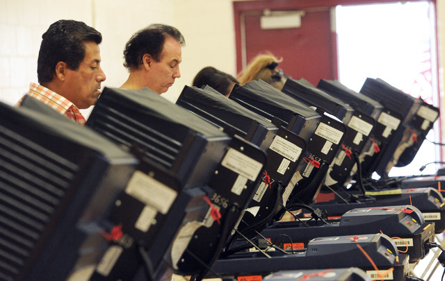 Tony Guerrero, left, works on his ballot as he and others vote at Cimarron-Memorial High School in Las Vegas, Tuesday, June 10, 2014. (Jerry Henkel/Las Vegas Review-Journal)
