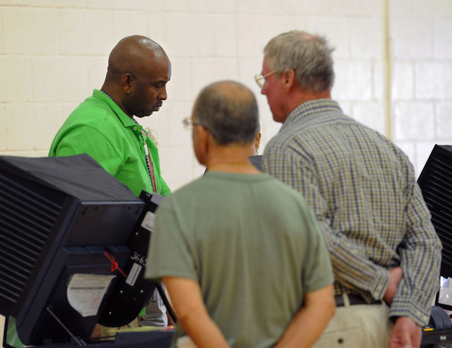 Team leader Charles Miller, left, and his team work on a technical glitch at the polling place at Cimarron-Memorial High School in Las Vegas, Tuesday, June 10, 2014. (Jerry Henkel/Las Vegas Review ...