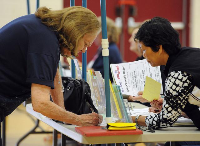 Poll worker Wilma Del Mundo, right, assists Verlene Wheeler as she registers to vote at Cimarron-Memorial High School in Las Vegas, Tuesday, June 10, 2014. (Jerry Henkel/Las Vegas Review-Journal)