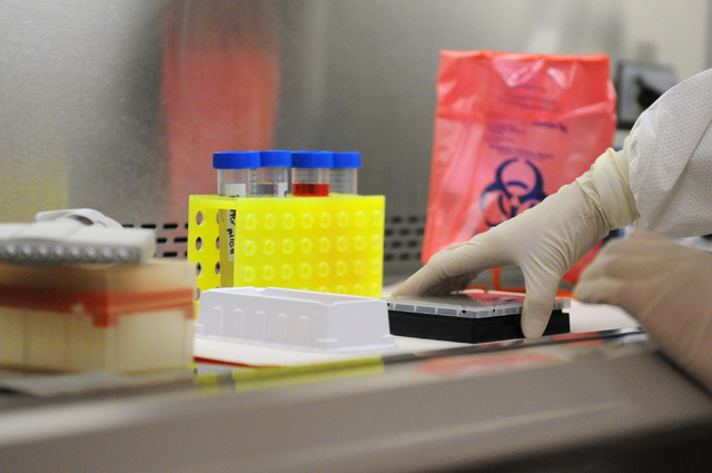 Susanne Quianzon, senior clinical laboratory scientist at Southern Nevada Public Health Laboratory in Las Vegas, processes a plate with pathogen samples at her work station during the facility's f ...