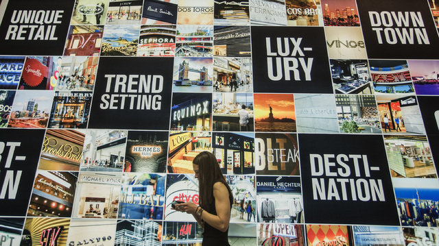 Retail marketing manager Tara Laney checks her phone  in the Brookfield Office Properties booth at the ICSC RECon convention inside  the Las Vegas Convention Center on Monday, May 19, 2014. The th ...