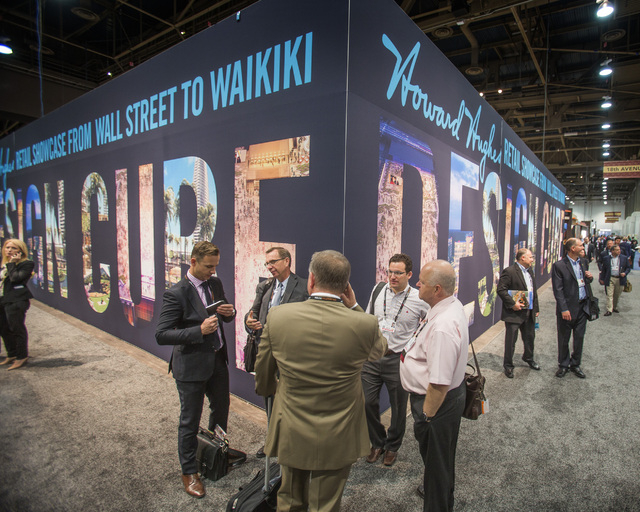 People stand beside the Howard Hughes Corp. booth at the ICSC RECon convention inside  the Las Vegas Convention Center on Monday, May 19, 2014. The three day global retail real estate convention d ...