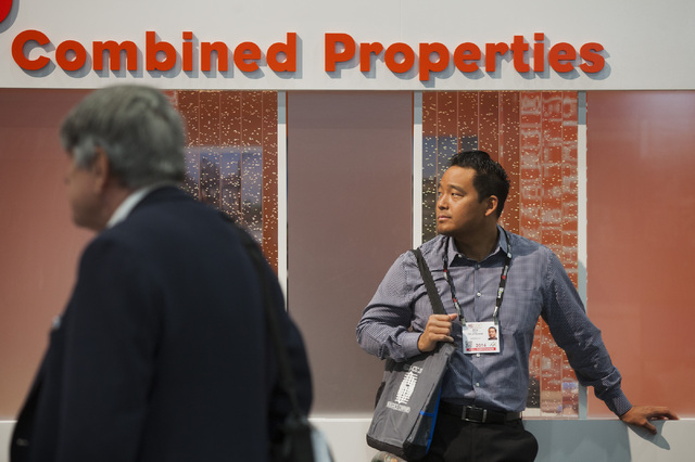 Bing Hyun, planning manager community development of City of Norwalk, Cal., stands near the Combined Properties booth during the ICSC RECon convention in  the Las Vegas Convention Center on Monday ...