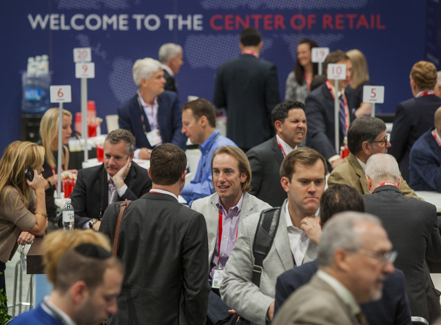 People gather in the Cushman & Wakefield booth during the ICSC RECon convention in  the Las Vegas Convention Center on Monday, May 19, 2014. The three day global retail real estate convention draw ...