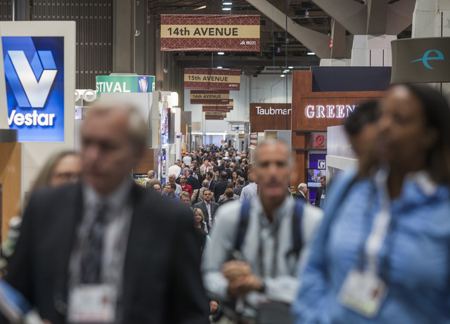 People walk during the ICSC RECon convention in  the Las Vegas Convention Center on Monday, May 19, 2014. The three day global retail real estate convention draws over 32,000 attendees and 1,000 e ...