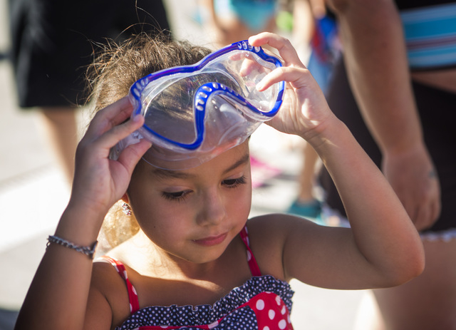 Jazz Kahanu, 6, adjusts her goggles before taking a swimming class at Wet'n'Wild Las Vegas on Friday, June 20, 2014. The theme park  participated in the world's largest simultaneous swimming lesso ...