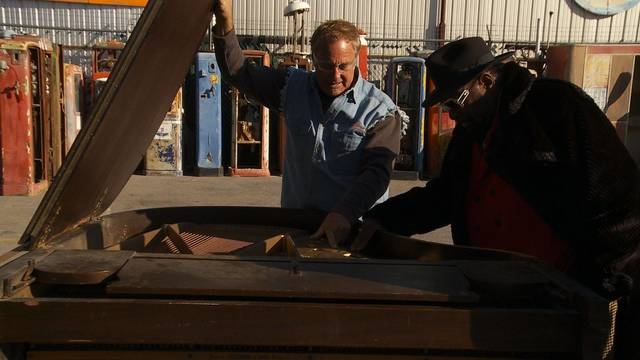 """George Clinton, right, shows Rick Dale the damage to his piano on """"American Restoration."""" (Photo by Leftfield Pictures)"""