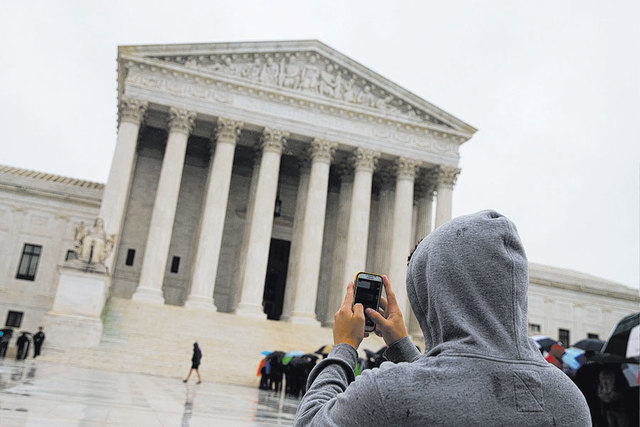 A visitor to the U.S. Supreme Court uses his cellphone to take a photo of the court in Washington on April 29, 2014. On Wednesday, a unanimous Supreme Court ruled that police may not generally sea ...