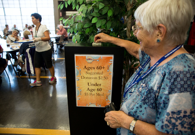 Helen Printz (cq) drops a donation for eating lunch at the Heritage Park Senior Facility in Henderson on Friday, June 20, 2014. In an effort to reduce taxpayer costs, the suggested donation price  ...