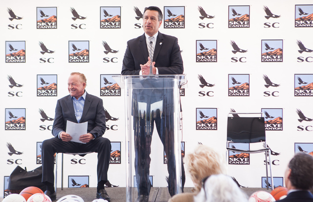Gov. Brian Sandoval, center, speaks as Garry Goett, CEO and chairman of Olympia Companies, which is the developer of the Skye Canyon master planned community, sits on left, during the groundbreaki ...